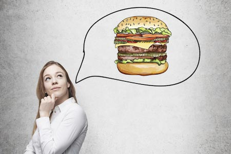 A beautiful woman is thinking about burger. A fast food concept. Concrete background