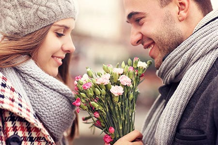 Couple celebrating date night with flowers between them