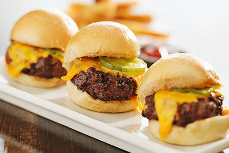 Delicious mini burgers lined up on plate with a lot of cheese
