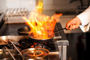 Chef flash frying a dish in pan
