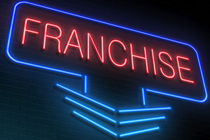 Neon sign lit up that says Franchise